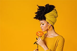 woman sniffing yellow and orange rose