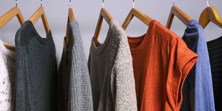 sweaters hanging up on hangers