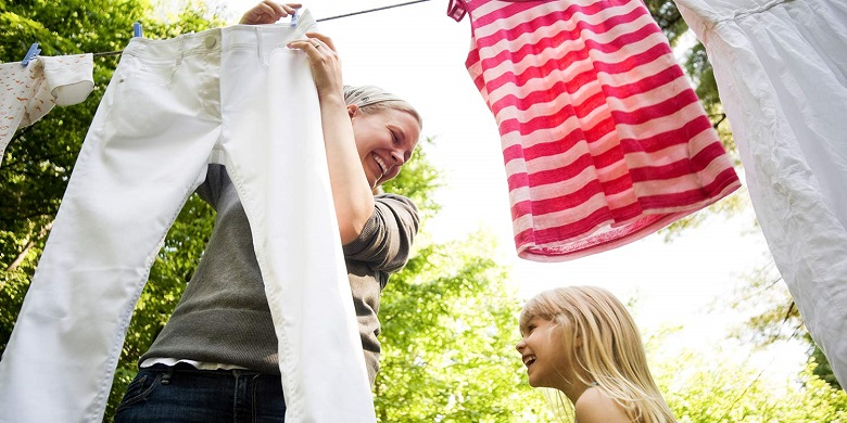 mom and daughter hanging clothes on a clothes line