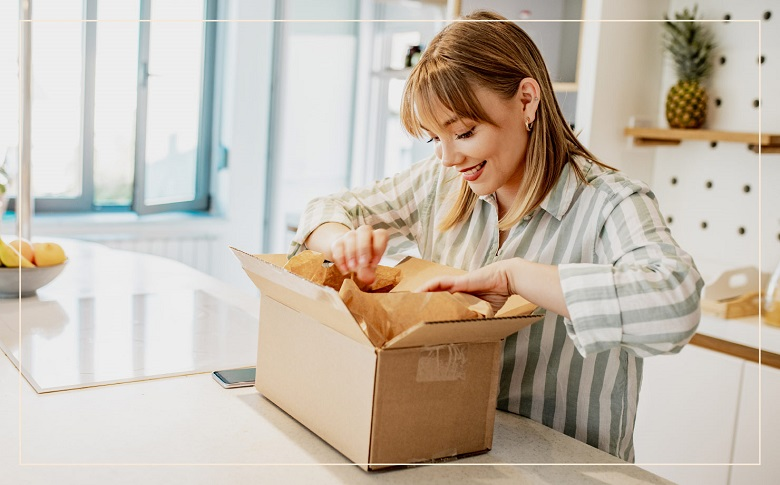 smiling woman opening cardboard box and tissue paper