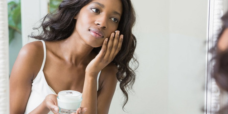 lady rubbing her face with lotion