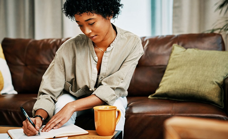 woman journaling on her couch