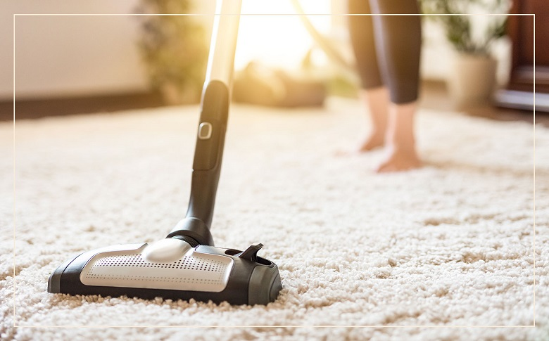 person vacuuming using a carpet refresher